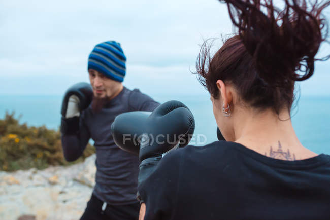 Man and woman in boxing gloves punching each other while standing on sea coast — Stock Photo