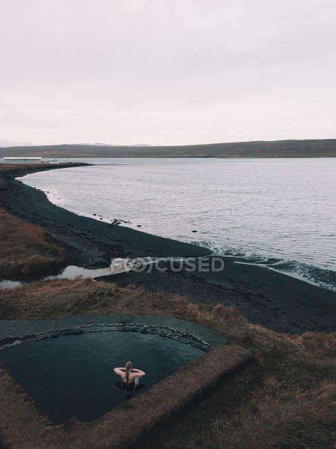 Берег моря с сухой травой и облачным небом и женщиной, отдыхающей в воде бассейна на заднем плане — стоковое фото