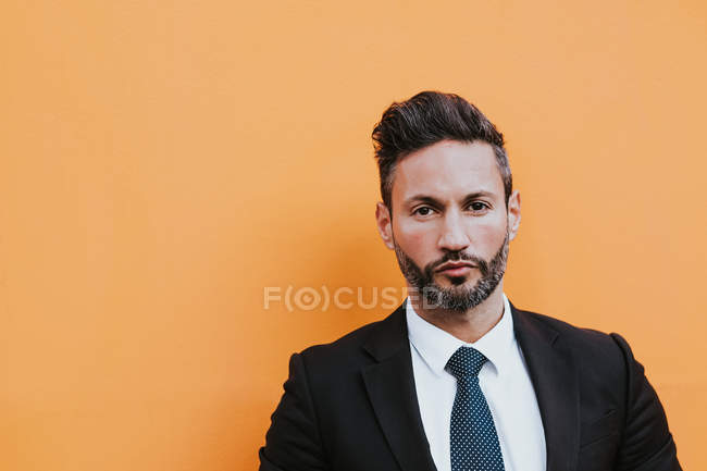 Adult handsome elegant businessman in formal suit adjusting jacket and looking at camera near orange wall — Stock Photo