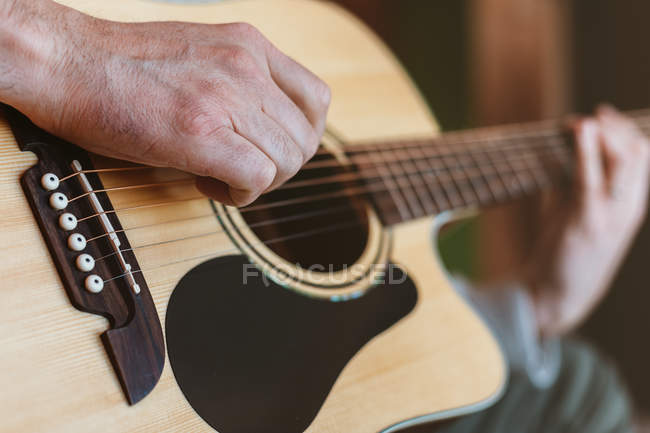 Hand of man playing guitar on blurred background — Stock Photo
