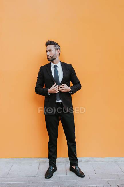 Adult handsome elegant businessman in formal suit adjusting jacket and looking away near orange wall — Stock Photo