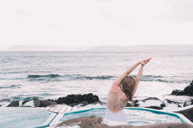 Back view of woman in swimsuit resting in water of pool near rocks and cloudy sky on sea coast — Foto stock