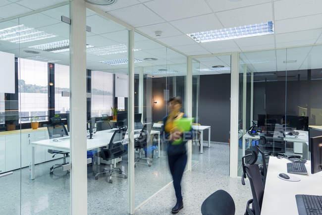 Размытые женщины-менеджер с папками с документами во время прогулки в современном офисе — стоковое фото