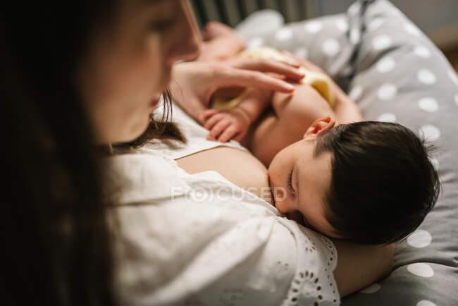 Дорослі самки обіймають і годують гарненьке новонароджене немовля, проводячи час вдома. — стокове фото