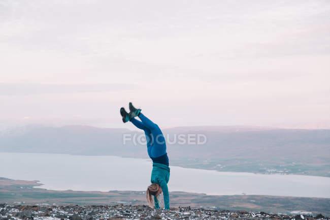 Блондинка, стоящая на руках на берегу — стоковое фото