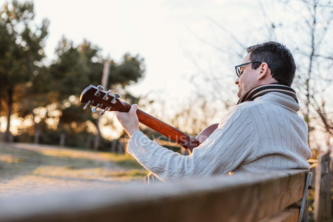 Casual man in eyeglasses playing guitar on bench in countryside — Fotografia de Stock