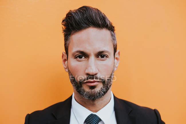 Un hombre de negocios joven y elegante con traje formal mirando a la cámara cerca de la pared naranja. - foto de stock