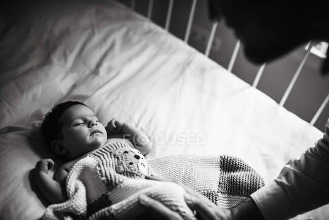 Чорно-білий урожай чоловік схилившись над колискою і торкаючись сплячого малюка м'яко в затишній дитячій кімнаті вдома. — стокове фото