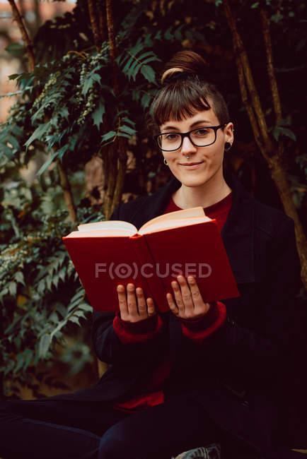 Молода усміхнена елегантна жінка в окулярах з книжкою сидячи на лавці в городі і дивлячись на камеру — стокове фото