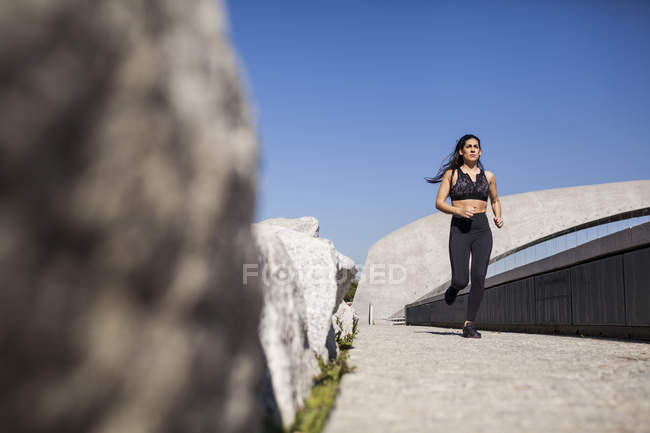 Young brunette slim woman in sportswear jogging in park in sunny day — Stock Photo