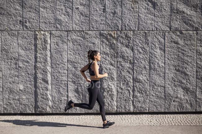 Брюнетка женщина работает на солнечное утро с гранитной стеной на заднем плане — стоковое фото