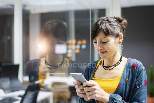Manager femminile sorridente utilizzando smartphone mentre in piedi vicino alla parete di vetro in ufficio moderno — Foto stock