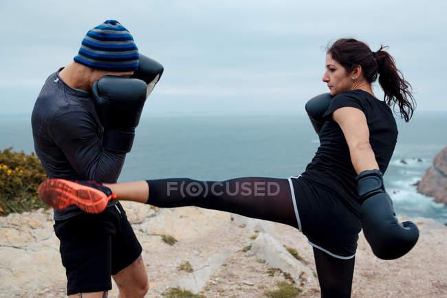 Чоловік і жінка в боксерських рукавичках пробиваючи один одного, стоячи на скелі проти моря і неба — стокове фото