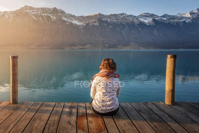 Vista trasera de la mujer sentada en el muelle de madera sobre el lago turquesa en las montañas nevadas de Suiza - foto de stock