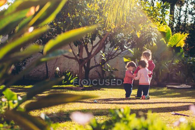 Tres niñas lindas jugando y tomándose de la mano en un círculo en un día soleado en un parque - foto de stock