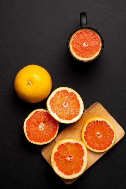 Sliced and whole grapefruits on black background near wooden board and mug — Stock Photo