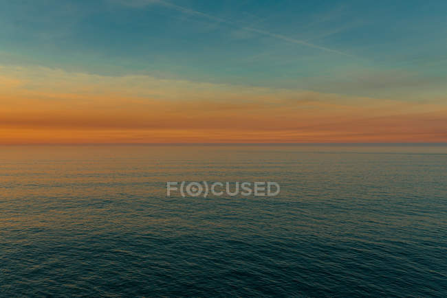 Minimalist landscape of calm rippled water of ocean with colorful sky at sunset, Spain — стоковое фото