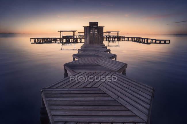 Jetée géométrique en bois vide au-dessus de l'eau calme sur fond de coucher de soleil lumineux — Photo de stock
