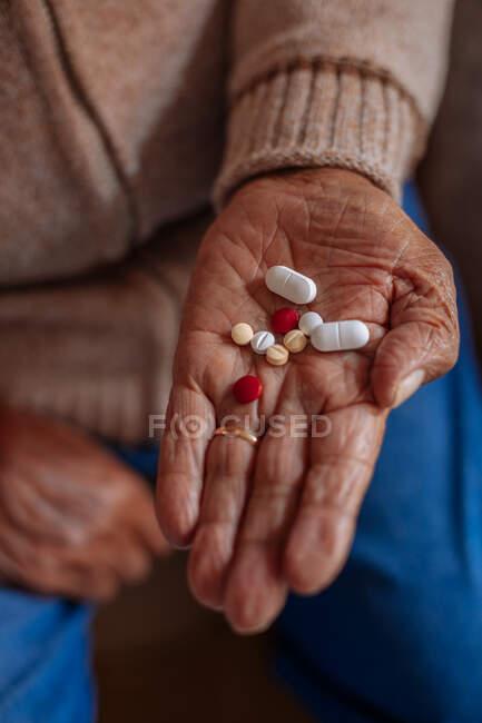 Detalhe de pílulas na mão de um homem velho — Fotografia de Stock