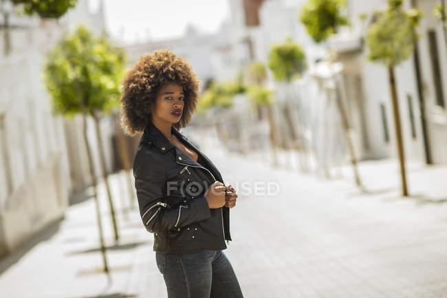 Привабливий афроамериканець жінка з Кучеряве волосся налаштування шкіряний піджак і дивлячись на камеру, стоячи на розмитому тлі вулиці міста в сонячний день — стокове фото