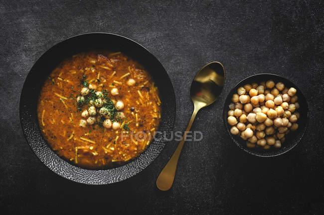 Soupe traditionnelle Harira pour Ramadan dans un bol noir sur une table sombre — Photo de stock