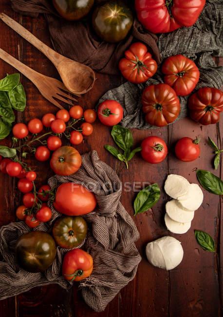 Pomodori freschi e mozzarella con foglie di basilico per insalata su superficie di legno e tovagliolo di tessuto — Foto stock