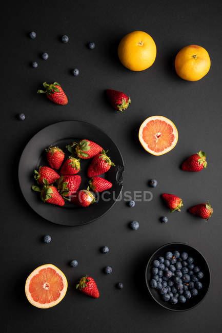 Різні свіжі фрукти і ягоди розкидані на чорному фоні — стокове фото