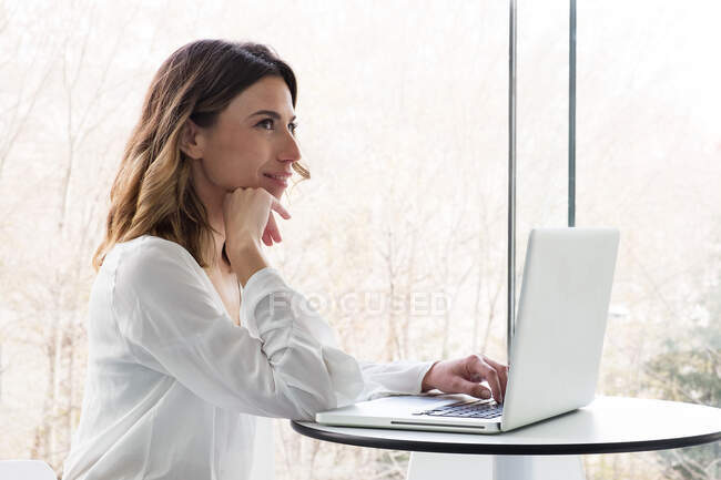 Woman sitting at table in a coffee shop browsing laptop near big windows — Stock Photo