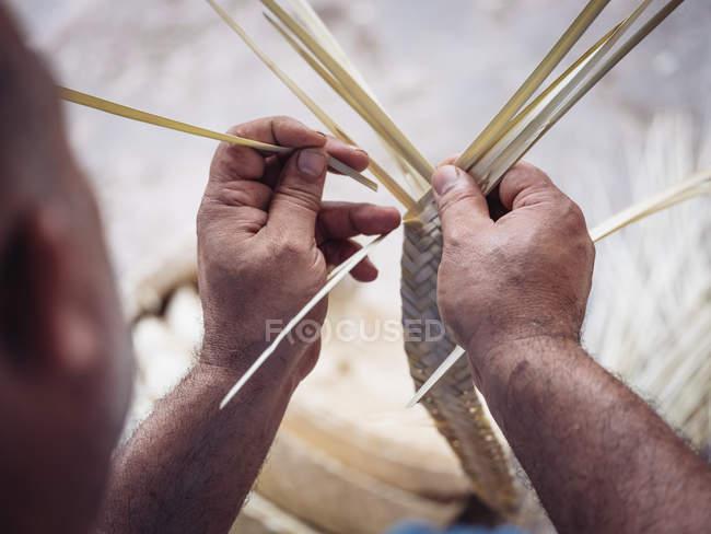 Mãos fechadas do artesão anônimo usando gancho para tecer a fibra seca das folhas de palma enquanto trabalhava na oficina — Fotografia de Stock