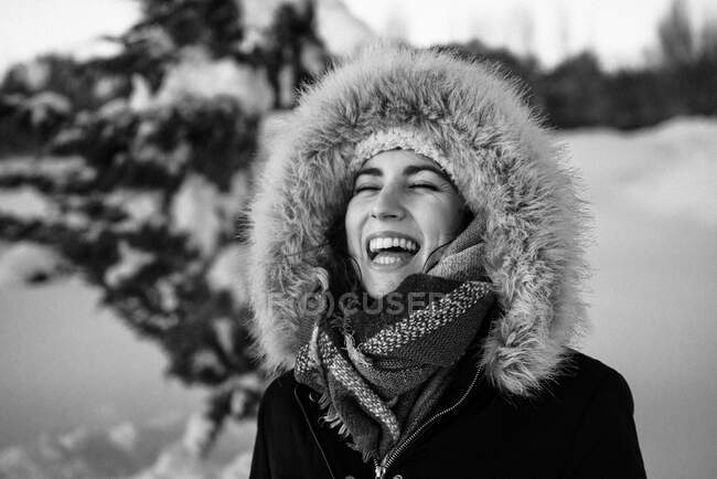 Young attractive female in warm clothing with fur joyful laughing beside covered snow conifer tree — Stock Photo