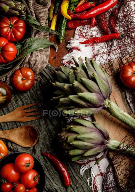 Conjunto de varias verduras frescas y servilletas de tela rústica en la mesa en la cocina - foto de stock