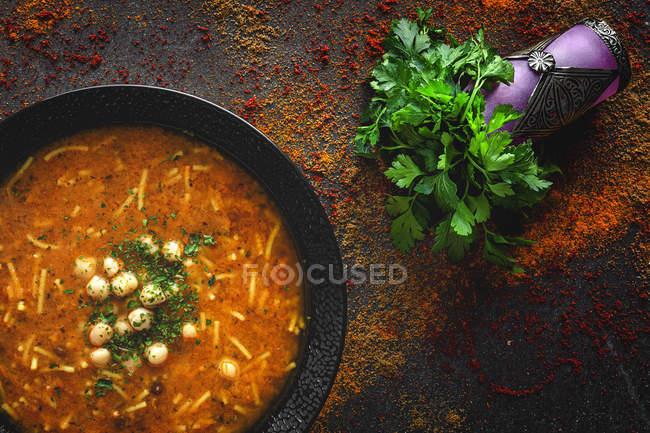 Soupe traditionnelle Harira pour Ramadan dans un bol noir sur une table sombre avec de la coriandre fraîche — Photo de stock
