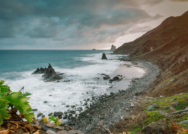 Picturesque view of rocky cliffs in amazing sea on dramatic cloudy day in Playa Benijo Tenerife Spain — Stock Photo