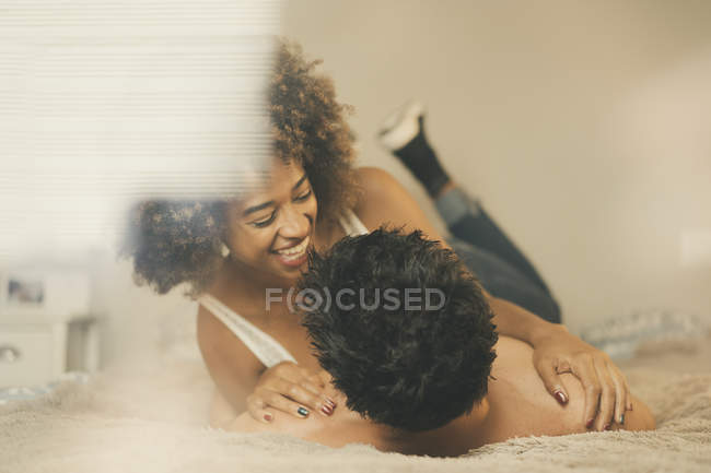 Young man and woman lying on bed and cuddling in cozy room at home — Fotografia de Stock