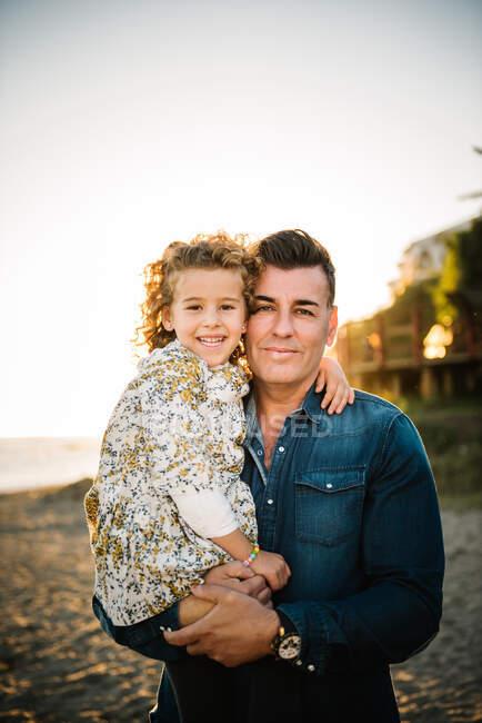 Середній літній чоловік з дочкою на березі моря посміхається і обіймає один одного — стокове фото
