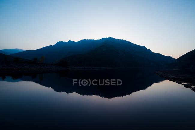 Pintoresca vista de la superficie del agua cerca de increíbles colinas rocosas al atardecer y el cielo azul - foto de stock