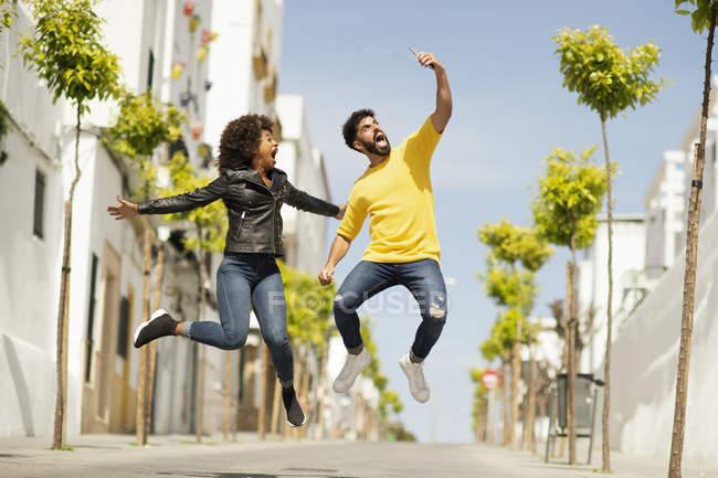 Hombre barbudo guapo y mujer bonita gritando y saltando mientras toma selfie en día soleado en la calle de la ciudad - foto de stock