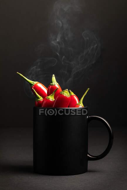 Caneca de cerâmica preta fumegante cheia de pimentas quentes colocadas contra fundo escuro — Fotografia de Stock
