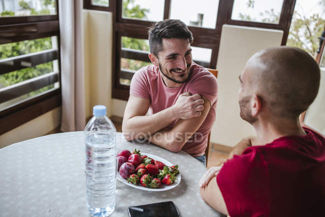 Gay couple talking at table with strawberries and plums — Stock Photo