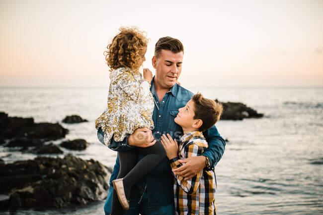 Чоловік середнього віку з дітьми на березі моря посміхається і обіймає один одного — стокове фото