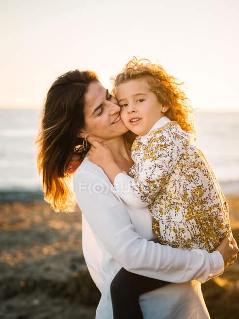 Mujer de mediana edad con su hija en la orilla del mar sonriendo y abrazándose - foto de stock