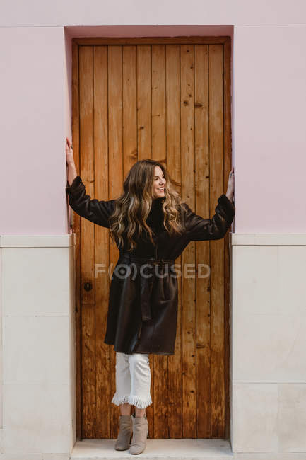 Smiling stylish woman in vintage leather coat standing near wooden door on street — Stock Photo