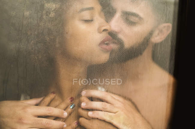 Handsome Hispanic guy touching and kissing seductive African American woman while standing behind wet window at home — Stock Photo