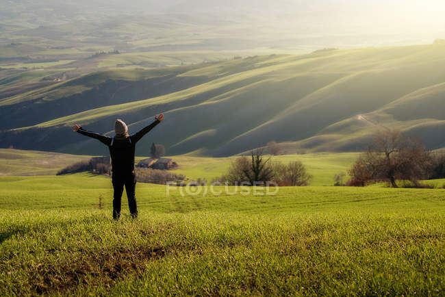 Back view of person in jacket with open arms in majestic green fields of Italy — Stock Photo