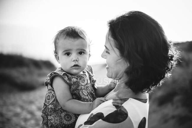Madre sosteniendo a un niño pequeño - foto de stock