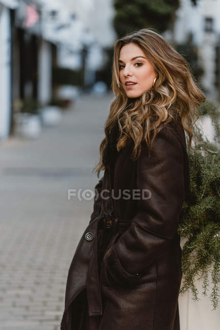 Attractive stylish woman standing on city street — Stock Photo