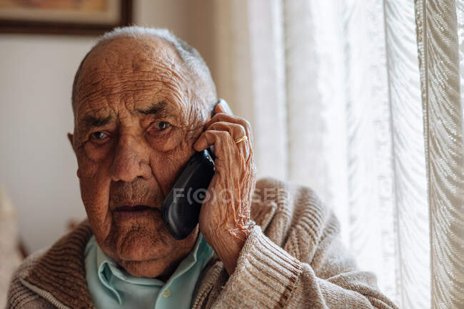 Elderly man calling from his phone inside his house — Stock Photo