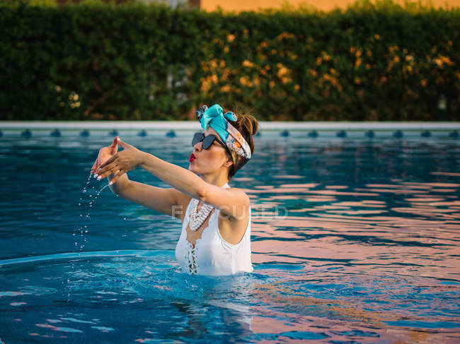Young rich chinese woman relaxing in swimming pool at luxurious resort — Foto stock