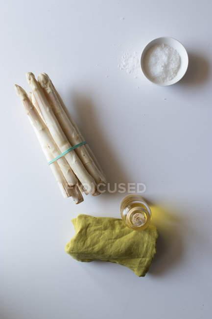 Зеленая салфетка на белом столе рядом с горсткой свежей спаржи с маслом и солью — стоковое фото