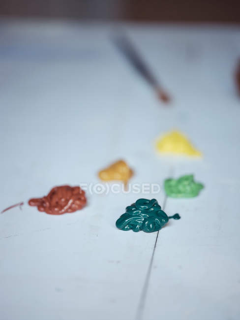 Colorful thick pigment squeezed on paper surface in workshop — стокове фото